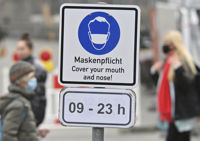 People wearing face masks walk past a sign saying 'Mask duty – Cover your mouth and nose!' in a pedestrian zone in the city center of Munich, Germany, Thursday, Oct. 15, 2020. German Chancellor Angela Merkel and Germany's 16 state governors agreed Wednesday night to tighten mask-wearing rules, make bars close early and limit the number of people who can gather in areas where coronavirus infection rates are high. (Peter Kneffel/dpa via AP)
