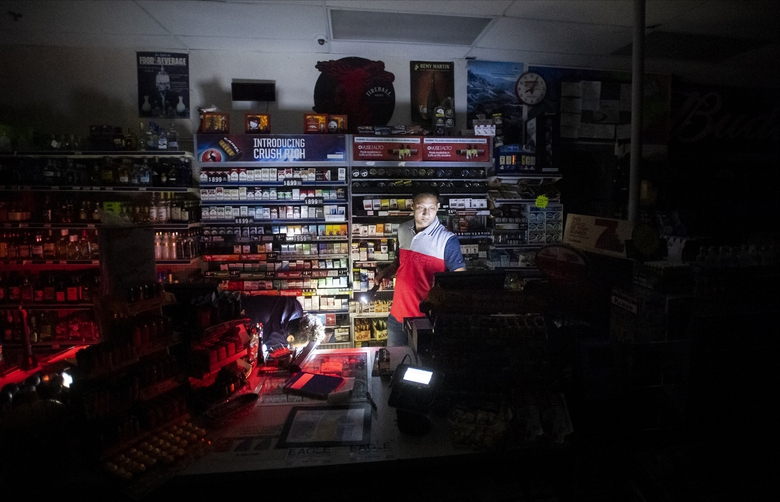 FILE – In this Saturday, Oct. 26, 2019, file photo, Sodhi Singh, closes up his Chevron station shortly after losing power in Healdsburg, Calif. Pacific Gas & Electric cut power Sunday, Oct. 25, 2020, to more than 100,000 California customers and planned outages for many more to prevent the chance of sparking wildfires because of extreme fire weather. More than 1 million people could be affected by planned outages as California braces for a return of gusty winds and bone-dry weather. As many as 361,000 customers in 36 counties could be affected by outages in northern California and another 83,000 customers in Southern California. (AP Photo/Noah Berger, File)