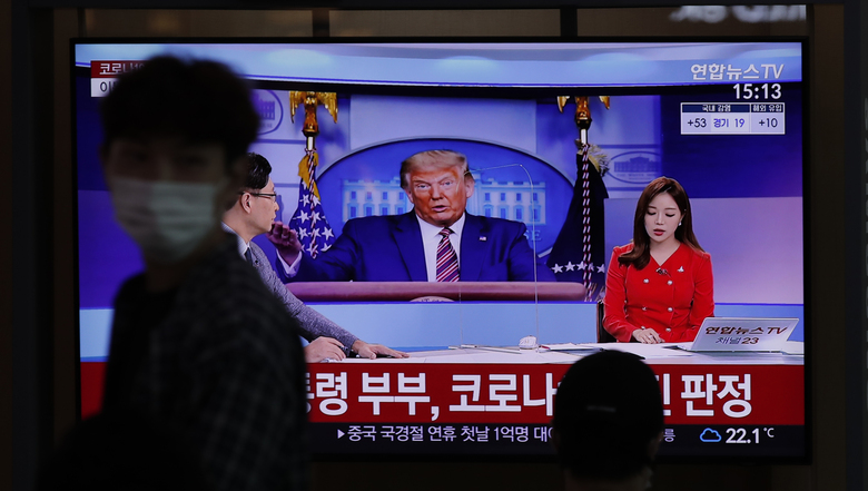 """A man wearing a face mask walks near a TV screen reporting about U.S. President Donald Trump and first lady Melania Trump during a news program with a file image of Trump at the Seoul Railway Station in Seoul, South Korea, Friday, Oct. 2, 2020. Trump said early Friday that he and Melania Trump have tested positive for the coronavirus, a stunning announcement that plunges the country deeper into uncertainty just a month before the presidential election. The Korean letters read: """"President Donald Trump and first lady Melania Trump tested positive for COVID-19."""" (AP Photo/Lee Jin-man)"""