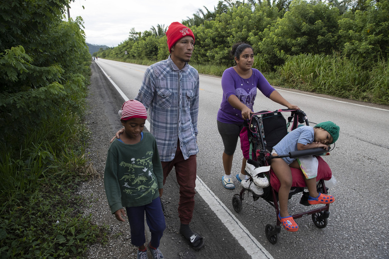 Honduras migrant Marcos Pineda, his wife Keysi Giron and their children Genesis and Ezequiel walk through San Luis Peten, Guatemala, Saturday, Oct. 3, 2020. Early Saturday, hundreds of migrants who had entered Guatemala this week without registering were being bused back to their country's border by authorities after running into a large roadblock. (AP Photo/Moises Castillo)