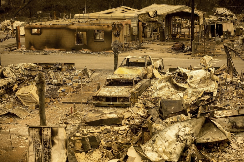 FILE – In this Aug. 20, 2020, file photo, scorched homes and vehicles fill Spanish Flat Mobile Villa following the LNU Lightning Complex fires in unincorporated Napa County, Calif. Deadly wildfires in California have burned more than 4 million acres (6,250 square miles) this year, a new record for the most acres burned in a single year. California fire officials said the state hit the fearsome milestone Sunday, Oct. 4, with about two months still left in the fire season.  (AP Photo/Noah Berger, File)