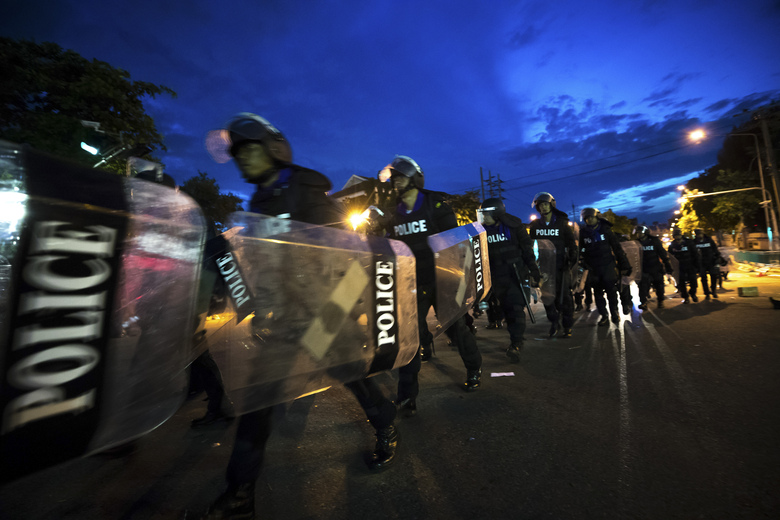 Riot Police move in with riot shields to disperse pro-democracy protesters from encroaching on the Government House in Bangkok, Thailand, Thursday, Oct. 15, 2020. Thousands of anti-government protesters gathered Wednesday for a rally at Bangkok's Democracy Monument being held on the anniversary of a 1973 popular uprising that led to the ousting of a military dictatorship, amid a heavy police presence and fear of clashes with political opponents. (AP Photo/Wason Wanichakorn)