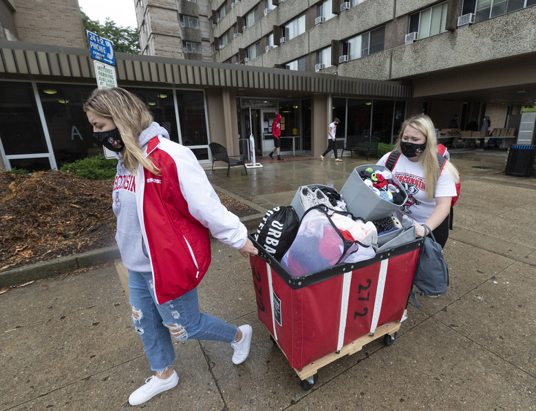 FILE – In this Sept. 10, 2020, file photo, Freshmen Lauren Tamborini and Bailey Donahue move out of Sellery Residence Hall the University of Wisconsin in Madison, Wis. President Donald Trump's startling COVID-19 diagnosis serves as a cruel reminder of the pervasive spread of the coronavirus in the United States and shows how tenuous of a grip the nation has on the crisis, health experts said. (Mark Hoffmann/Milwaukee Journal-Sentinel via AP, File)