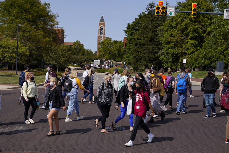 FILE – In this Sept. 10, 2020, file photo, masked students cross an intersection on the campus of Ball State University in Muncie, Ind. President Donald Trump's startling COVID-19 diagnosis serves as a cruel reminder of the pervasive spread of the coronavirus in the United States and shows how tenuous of a grip the nation has on the crisis, health experts said. (AP Photo/Michael Conroy, File)