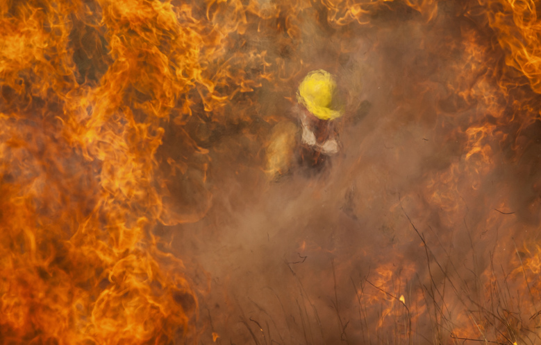 A firefighter battles flames in Capilla del Monte, Cordoba, Argentina, Thursday, Oct. 15, 2020. During Wednesday night a light rain extinguished all the fires in the province but by that afternoon the fire returned with the increasing temperatures, as the situation worsens due to the extensive drought Córdoba has been experiencing. (AP Photo/Mario Tizon)