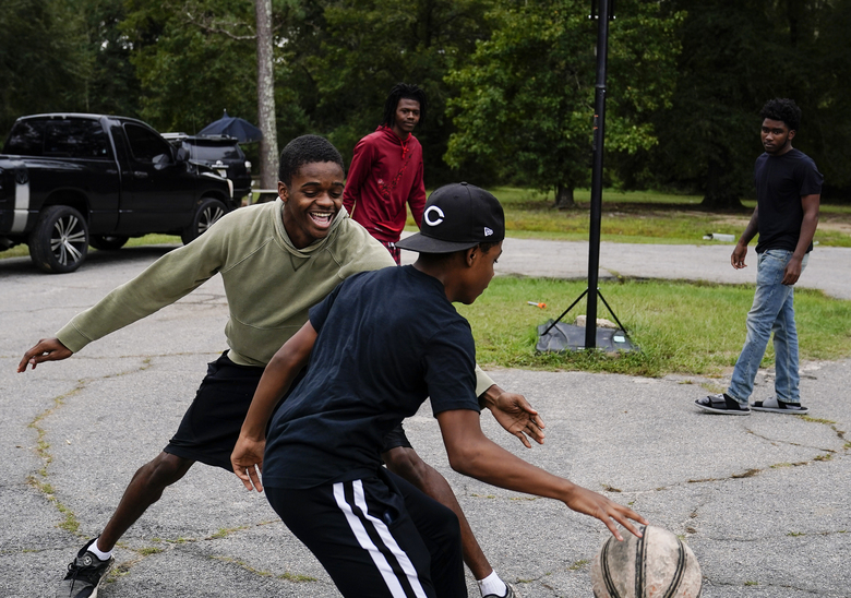 "JJ Ivey, 13, center, Jay Johnson, 19, left, Te Moss, 18, back left, and Voen Ivey, 18, right, play basketball in their neighborhood in Hancock County, Saturday, Sept. 19, 2020, in Mayfield, Ga. Early on, victims of the coronavirus were mostly residents of the county's two nursing homes. Now, it's younger residents too. Coroner Adrick Ingram sees young people in town not wearing masks and gathering in big groups, and it frustrates him. ""I see people who aren't taking it seriously, maybe because they don't see what I see. They don't get to look in people's faces when they've lost somebody."" (AP Photo/Brynn Anderson)"