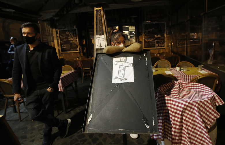 A drawing of a cross is placed outside an empty restaurant in Rome's Campo de' Fiori square, a popular evening spot of restaurants and pubs, to protest against the closing of the square, Friday, Oct. 23, 2020. (AP Photo/Alessandra Tarantino)