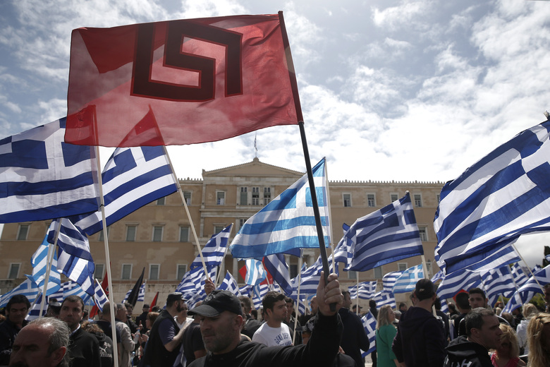 FILE – In this Wednesday, June 4, 2014 file photo, Golden Dawn supporters hold the party flag and Greek national flags during a rally outside Parliament in Athens. Greek police officials they are planning to deploy about 2,000 officers around Athens as the leadership of the extreme right group Golden Dawn faces a landmark criminal trial verdict. Eighteen former lawmakers from the party founded in the 1980s as a neo-Nazi organization are among 69 defendants who have been on trial for the past five years. The verdict is expected Wednesday Oct. 7, 2020. (AP Photo/Petros Giannakouris)