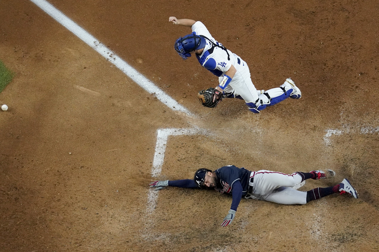 Atlanta Braves' Nick Markakis scores past Los Angeles Dodgers catcher Will Smith on a double by Cristian Pache during the fifth inning in Game 2 of a baseball National League Championship Series Tuesday, Oct. 13, 2020, in Arlington, Texas. (AP Photo/David J. Phillip)