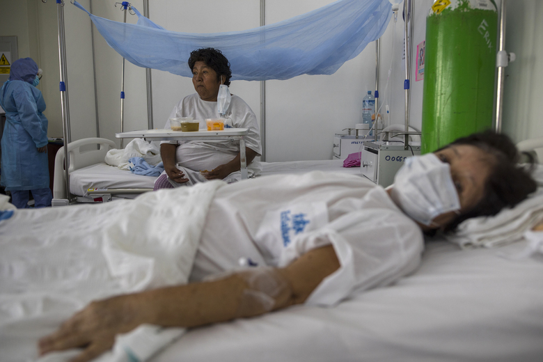 """Lidia Choque eats her lunch in a ward designated for patients diagnosed with dengue and the new coronavirus, at a public hospital in Pucallpa, in Peru's Ucayali region, Saturday, Oct. 3, 2020. The 53-year-old woman stayed nearly two weeks in the ward with eight female dengue patients, riddled with anxiety over her condition. """"I felt desperate,"""" she said. (AP Photo/Rodrigo Abd)"""