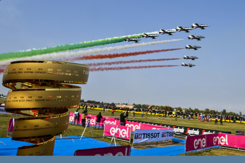 The Giro d'Italia trophy is backdropped by the Frecce Tricolori Italian Air Force aerobatic squad flying past, prior to the 15th stage of the Giro d'Italia cycling race, Italy, at the Rivolto air base, Sunday, Oct. 18, 2020. (Marco Alpozzi/LaPresse via AP)