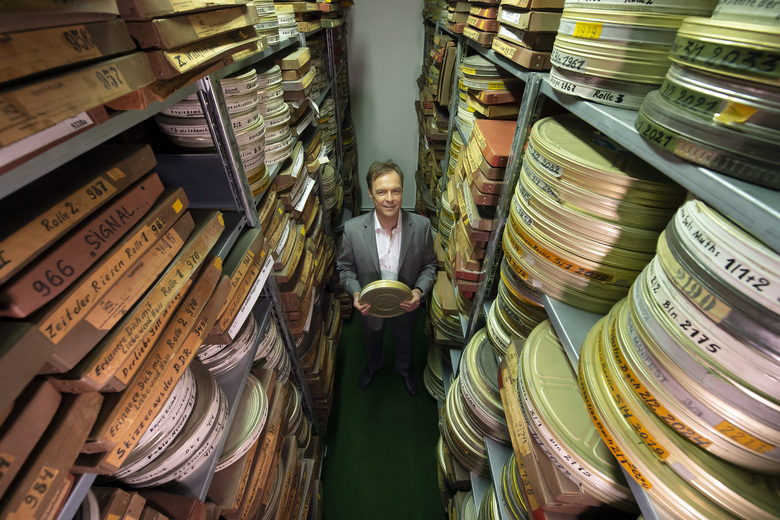 In this Wednesday, June 17, 2020 photo Gunnar Dedio, German film producer and managing director of PROGRESS Film GmbH poses for a photo between rolls of film in the archive of PROGRESS Film, in Leipzig, Germany. A new project is underway to digitize thousands of East German newsreels, documentaries and feature films 30 years after Germany's reunification. The movies that are being scanned, transcribed and posted online provide a look inside a country that no longer exists but was a critical part of the Cold War. (AP Photo/Jens Meyer)