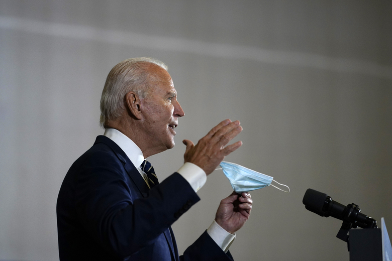 Democratic presidential candidate former Vice President Joe Biden holds a mask as he speaks at Beech Woods Recreation Center, in Southfield, Mich., Friday, Oct. 16, 2020. (AP Photo/Carolyn Kaster)