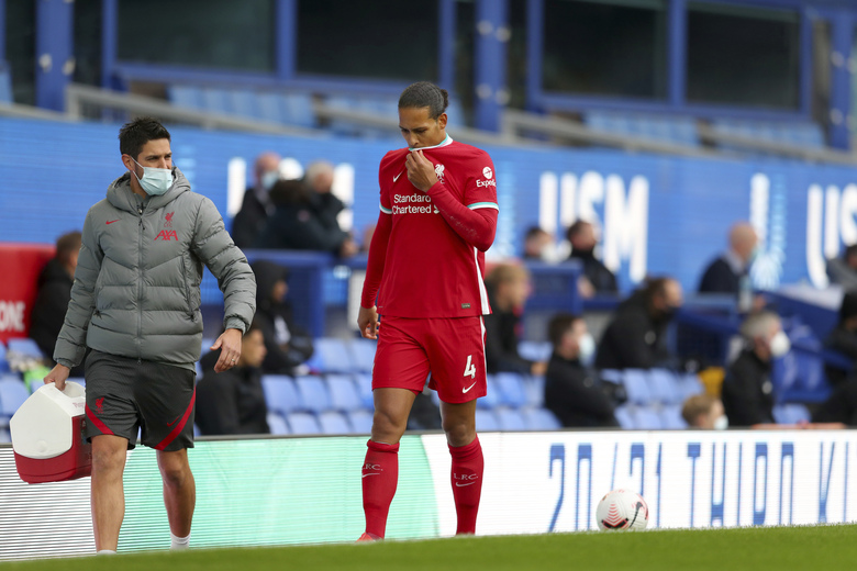 Liverpool's Virgil van Dijk leaves the match with an injury during the English Premier League soccer match between Everton and Liverpool at Goodison Park stadium, in Liverpool, England, Saturday, Oct. 17, 2020. (Cath Ivill/Pool via AP)