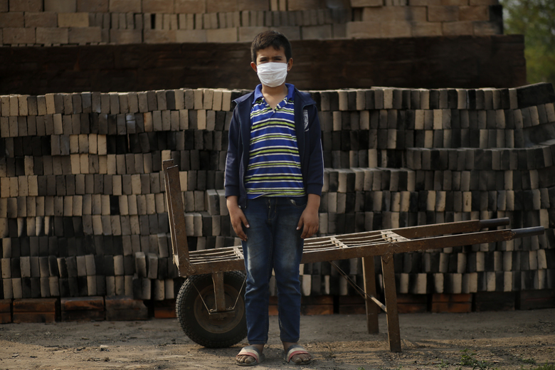 Ronnie, 10, wearing a mask to curb the spread of the new coronavirus, poses for a portrait as he works alongside his father at a small brick factory in Tobati, Paraguay, on Aug. 31, 2020. Members of brickmaking families said school closures, scheduled to last at least until December, have led to many children and adolescents working longer hours, making it difficult to complete their virtual schoolwork. (AP Photo/Jorge Saenz)