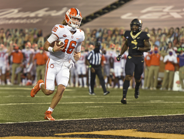 FILE  – In this Sept., 12, 2020, file photo, Clemson quarterback Trevor Lawrence scores against Wake Forest during the first half of an NCAA college football game, in Winston-Salem, N.C. Miami Hurricanes quarterback D'Eriq King leads an offense that has been among the most productive in the nation so far this season, but on Saturday he'll be going against Trevor Lawrence and top-ranked Clemson. (Walt Unks/The Winston-Salem Journal via AP, File)