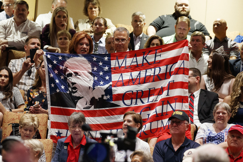 FILE – In this Thursday, Oct. 3, 2019 file photo, supporters of President Donald Trump hold a flag before he arrives to deliver remarks on Medicare at the Sharon L. Morse Performing Arts Center in The Villages, Fla. (AP Photo/Evan Vucci)