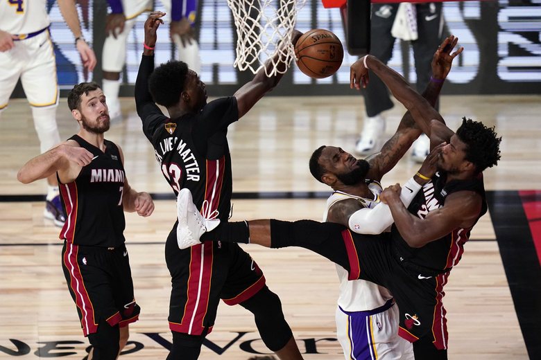 Miami Heat's Bam Adebayo (13) and Jimmy Butler (22) rejects a shot by Los Angeles Lakers' LeBron James (23) during the first half in Game 6 of basketball's NBA Finals Sunday, Oct. 11, 2020, in Lake Buena Vista, Fla. (AP Photo/John Raoux)