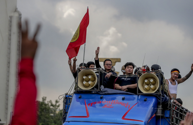 Pro-democracy leaders Parit Chiwarak, center right and Arnon Nampha, center left travel in a truck during a street march in Bangkok, Thailand, Wednesday, Oct. 14, 2020. Thousands of anti-government protesters gathered Wednesday for a rally being held on the anniversary of a 1973 popular uprising that led to the ousting of a military dictatorship, amid a heavy police presence and fear of clashes with political opponents. (AP Photo/Gemunu Amarasinghe)