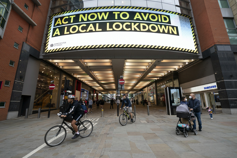 "FILE – In this Tuesday Sept. 22, 2020 file photo, members of the public are seen by a public information message in Manchester, England. The British government is under pressure to develop a national strategy to combat the second wave of the COVID-19 pandemic and ""rescue Christmas'' as scientists warn the number of people hospitalized with the disease could almost triple by the end of next month unless something is done now. (AP Photo/Jon Super, file)"