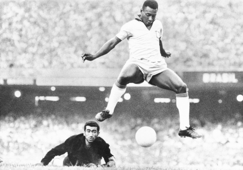 FILE – In this Aug. 1969 file photo, Brazil's Pele scores past Venezuela's goal keeper Fabrizio Fasano in Rio de Janeiro, Brazil. On Oct. 23, 2020, the three-time World Cup winner Pelé turns 80 without a proper celebration amid the COVID-19 pandemic as he quarantines in his mansion in the beachfront city of Guarujá, where he has lived since the start of the pandemic. (AP Photo, File)