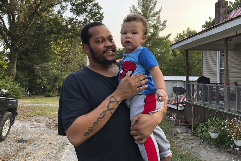 """Nicholas Lewis holds son, Nick Jr., near their home in Vienna, Ill., on Sunday, Sept. 27, 2020. Nick Jr.'s grandmother, Maribeth Harris, says """"It's our sanctuary,"""" of the street where they live. One of her daughters lives next door. Another lives across the street with her boyfriend, Lewis. Three grandkids live with her while Lewis takes care of the fourth. Harris, her husband and their daughters are white. Lewis says, """"I feel scared or just even strange going around to the store, because I know all eyes are on me."""" (AP Photo/Noreen Nasir)"""