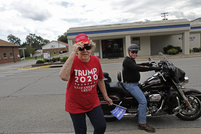 Doris Miller 86, left, adjusts her cap after getting off the back of a motorcycle belonging to Jeff Bundren, 60, Sunday, Aug. 2, 2020, in Vienna, Ill. This is a deeply conservative part of the nation _ 77 percent of the county voted for President Donald Trump in the 2016 elections; just 19 percent went for Hillary Clinton. (AP Photo/Wong Maye-E)