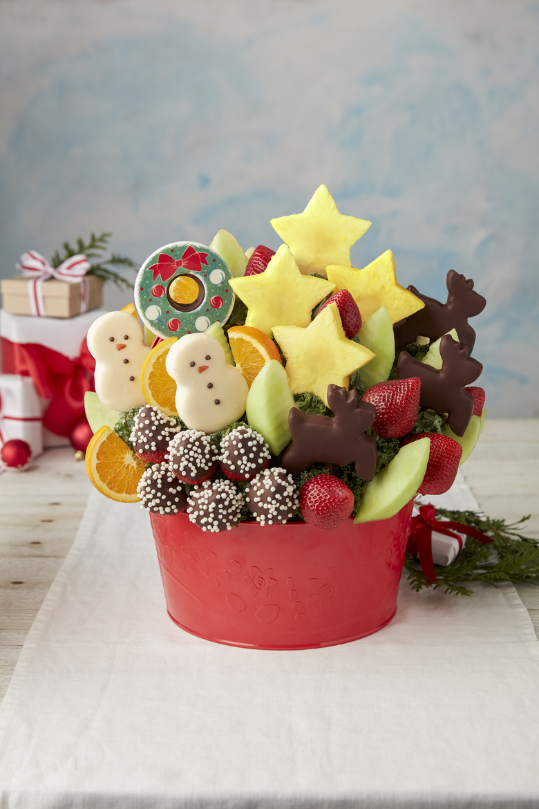 This image shows a holiday Edible Arrangement with a Christmas wreath and pineapple chocolate-covered snowmen and reindeer, starting at $74.99. (Edible via AP)