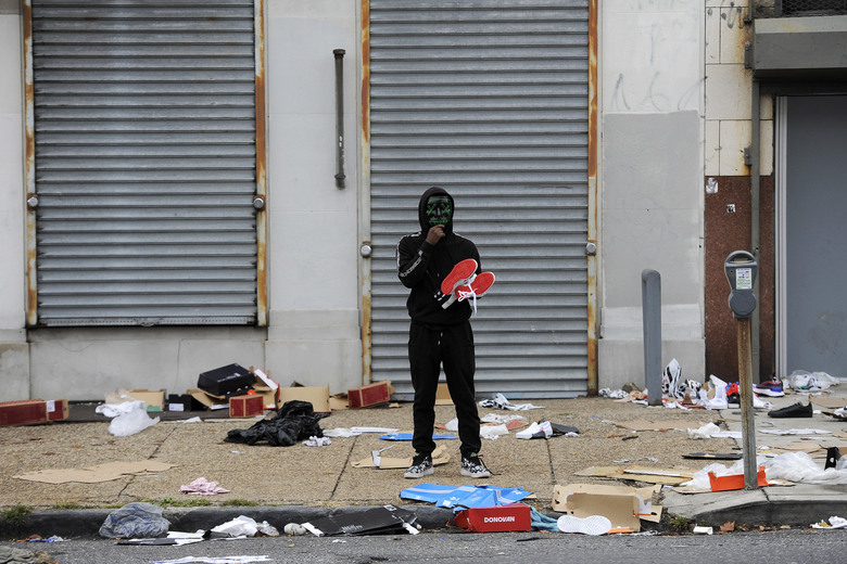 A man stands holds merchandise outside of a damaged store after protest, Tuesday, Oct. 27, 2020, in Philadelphia over the death of Walter Wallace, a Black man who was killed by police in Philadelphia. Police shot and killed the 27-year-old on a Philadelphia street after yelling at him to drop his knife, sparking violent protests that police said injured 30 officers and led to dozens of arrests. (AP Photo/Michael Perez)