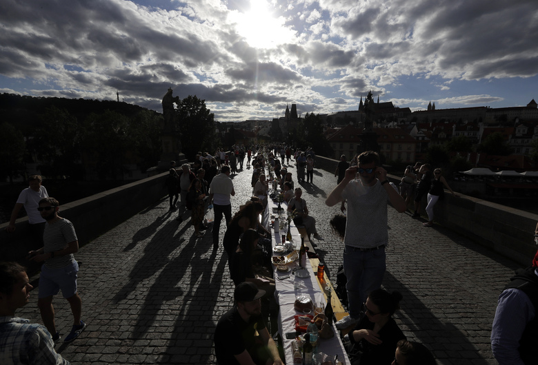 """FILE – In this  June 30, 2020, file photo, residents sit to dine on a 500 meter long table set on the medieval Charles Bridge, after restrictions were eased following the coronavirus pandemic in Prague, Czech Republic. The Czech Republic's """"Farewell Covid"""" party in June, when thousands of Prague residents dined outdoors at a 500-meter (yard) long table across the Charles Bridge to celebrate their victory over the virus, seems painfully naive now that the country has the highest per-capita infection rate on the continent. (AP Photo/Petr David Josek, File)"""