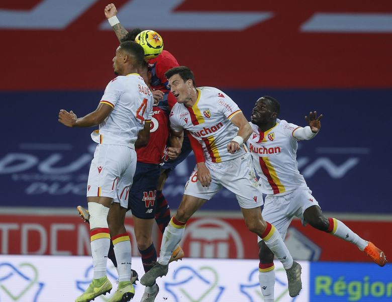 Lens' Loic Bade, left, and Manuel Perez, center, fight for the ball during their French League One soccer match between Lille and Lens in Villeneuve d'Ascq, northern France, Sunday Oct. 18, 2020. (AP Photo/Michel Spingler)