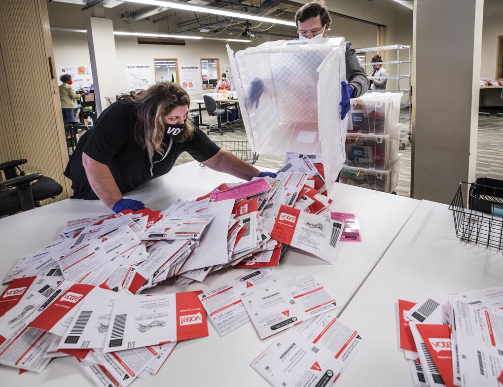 King County Elections workers Devon Lang, left, and Dmitry Verein sort  incoming ballots from drop boxes around the county on Tuesday. (Steve Ringman / The Seattle Times)