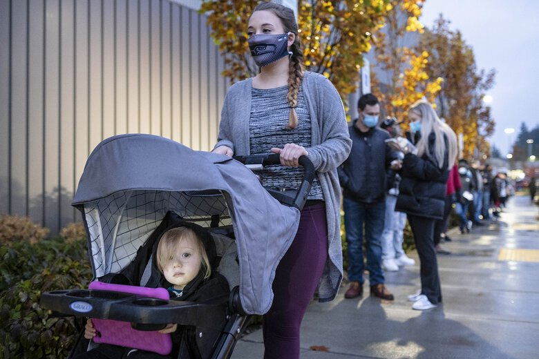 Quinn, 2, peeks up from her tablet for a moment as her mother, Nicole, stands in the quick-moving line for voters outside the Federal Way Performing Arts and Events Center on Tuesday. (Dean Rutz / The Seattle Times)