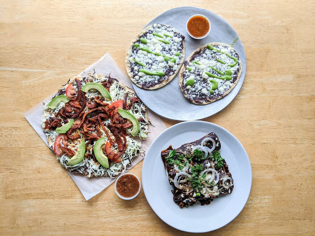 Casa Oaxaca in Edmonds specializes in traditional Oaxacan cuisine, including, from left clockwise, a crisp tlayuda with sliced pork, black-bean-topped memelas and rich mole negro. (Jackie Varriano / The Seattle Times)