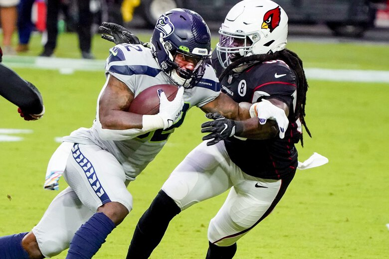 Seattle Seahawks running back Chris Carson (32) runs as Arizona Cardinals outside linebacker De'Vondre Campbell defends during the first half of an NFL football game, Sunday, Oct. 25, 2020, in Glendale, Ariz.  (Rick Scuteri / AP)
