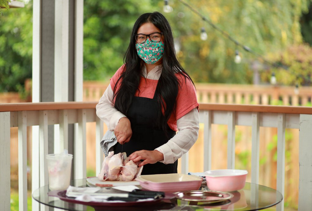 Kristina Glinoga, a Seattle-based butcher and sustainable food advocate, is photographed at her home in Ballard Nov. 5, 2020. Glinoga wears a mask decorated with flowers and cows, made by her boyfriend's mother, Kristine Coleman. (Erika Schultz / The Seattle Times)