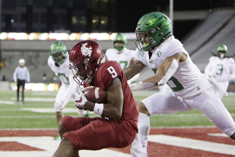 Washington State wide receiver Renard Bell, left, catches a pass for a touchdown in front of Oregon safety Nick Pickett during the first half of an NCAA college football game in Pullman, Wash., Saturday, Nov. 14, 2020. (AP Photo/Young Kwak) WAYK102 WAYK102 (Young Kwak / The Associated Press)