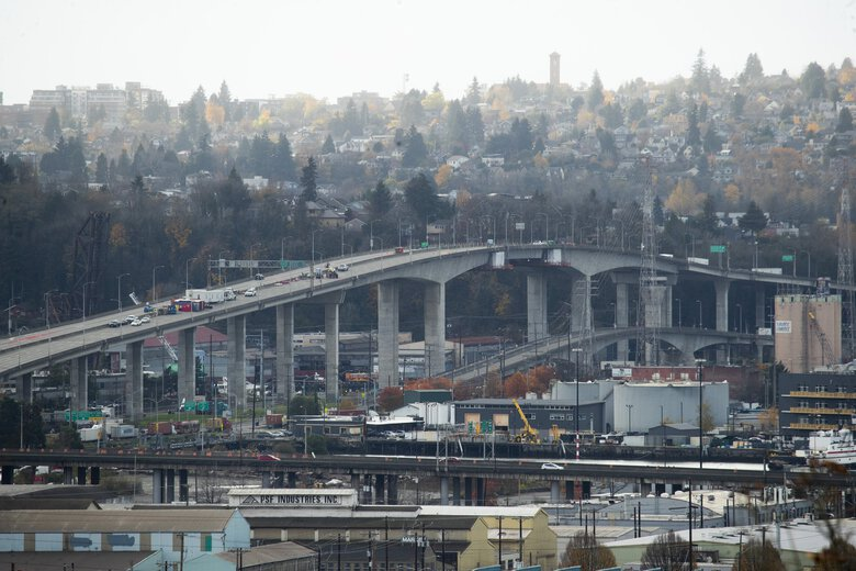Crews working to stabilize the West Seattle Bridge are staged on the deck of the closed structure, seen from Beacon Hill on Thursday. Mayor Jenny Durkan said the city intends to repair the bridge rather than replace the cracked span.  (Erika Schultz / The Seattle Times)