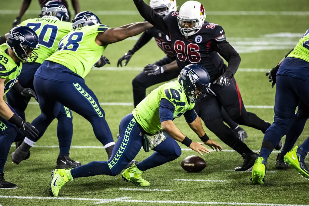 Seahawks quarterback Russell Wilson loses the snap but the Seahawks recovering the first quarter as the Seattle Seahawks take on the Arizona Cardinals for Thursday Night Football at Lumen Field in Seattle. (Bettina Hansen / The Seattle Times)