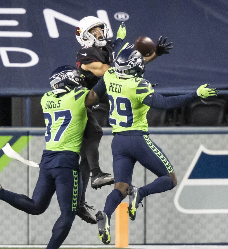 Quandre Diggs, left, and D.J. Reed deny Arizona receiver Andy Isabella a shot at a touchdown in the 4th quarter. (Dean Rutz / The Seattle Times)