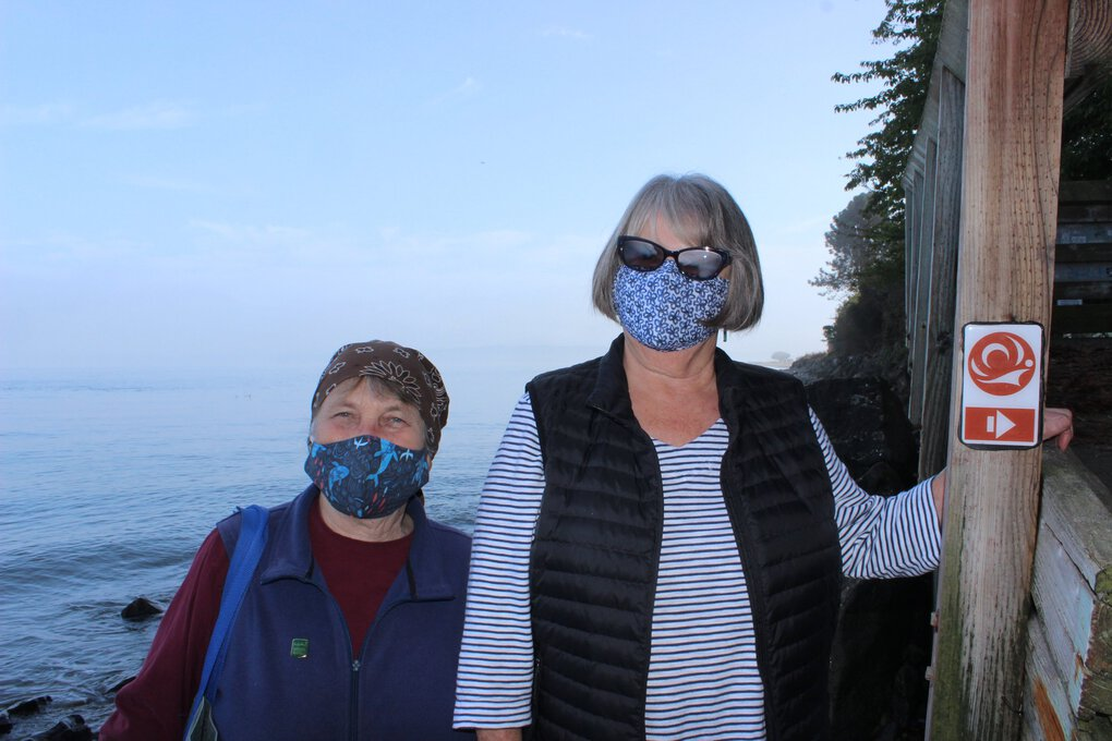Port Townsend residents and literal trailblazers Lys Burden, left, and Barbara Jo Blair pose for a photo on a portion of the čičməhán Trail that runs along the beach at low tide in Port Townsend. The trail blaze directs walkers off the beach and into Chetzemoka Park, one of 18 stops on the trail. (Gregory Scruggs / Special to The Seattle Times)