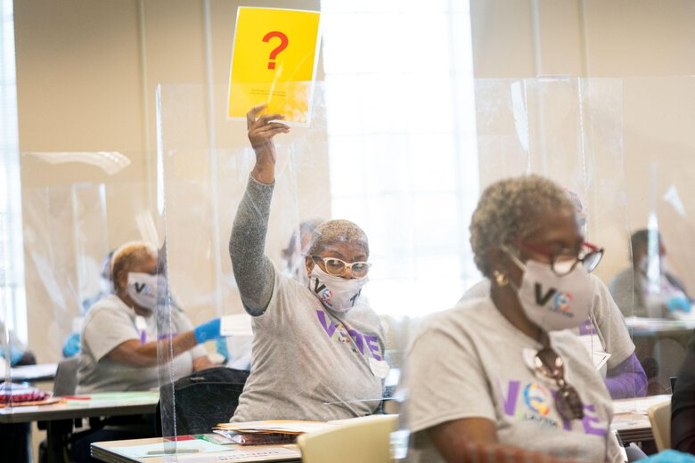 A Clayton County election worker holds up a sign signaling she needs help with determining a vote during a hand recount for the presidential election in Georgia last week. The state is the first of those where President Trump has mounted legal challenges to certify its results, confirming a 12,284-vote lead for former vice president Joe Biden. (Kevin D. Liles / For The Washington Post)