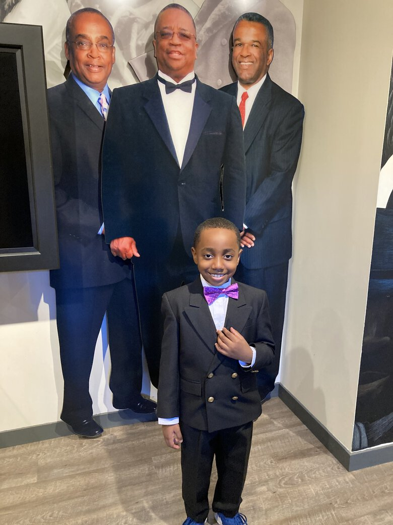 Seven-year-old A. Fitzgerald Bell II, posing before cutout portraits of Norman Rice, Larry Gossett and Ron Sims, virtually welcomed visitors to the Northwest African American Museum during its online Unity gala, presented on Oct. 22. (Courtesy of NAAM)