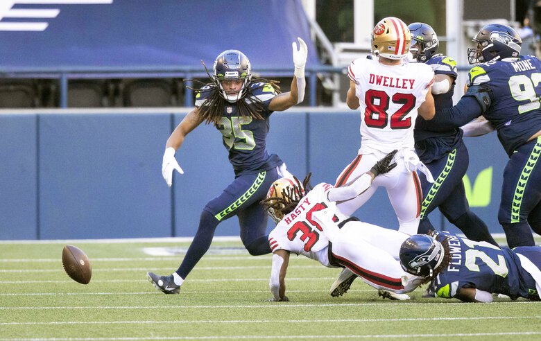 Niners running back JaMychal Hasty fumbles in the 1st quarter, with the ball initially ruled recovered by the Seahawks, but the 49ers kept possession upon review. (Dean Rutz / The Seattle Times)
