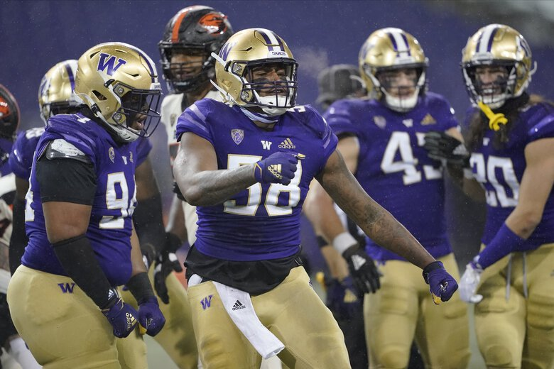 Washington's Sam Taimani, left, and Zion Tupuola-Fetui (58) react against Oregon State during the first half of an NCAA college football game, Saturday, Nov. 14, 2020, in Seattle. (Ted S. Warren / The Associated Press)