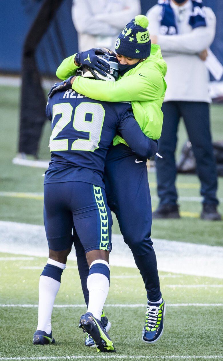 Seahawks cornerback D.J. Reed gets congratulated by injured safety Jamal Adams on his interception in the first half. (Bettina Hansen / The Seattle Times)