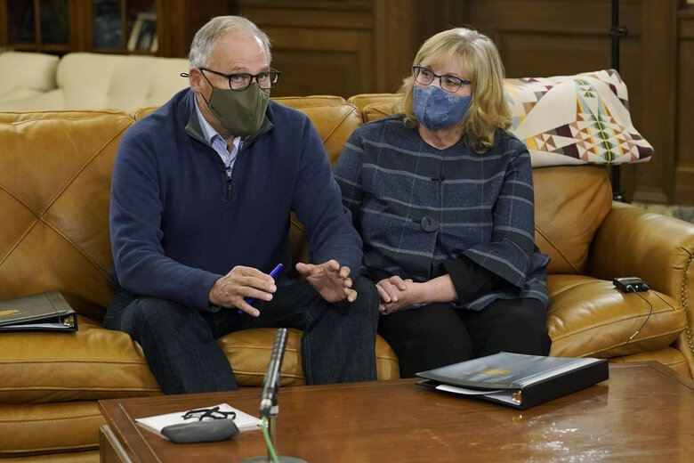 Washington Gov. Jay Inslee and his wife, Trudi, prepare for a final rehearsal in the governor's office Thursday before their  televised address on the spread of the coronavirus, which health officials have warned is accelerating rapidly across the state. (Ted S. Warren / The Associated Press)