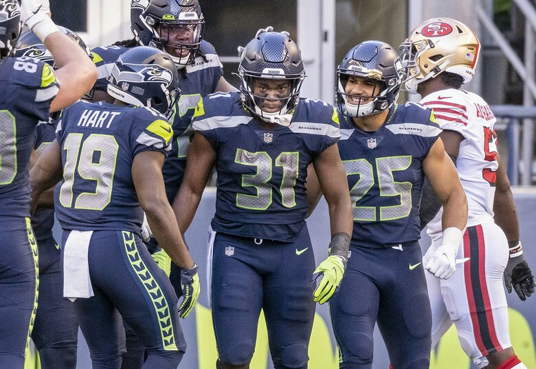The Seahawks congratulate DeeJay Dallas on his 3rd quarter touchdown Sunday against the 49ers. (Dean Rutz / The Seattle Times)