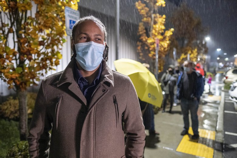 It's a light rain, but that doesn't stop 28-year old Kejuan Jones from standing in line outside Federl Way's polling place at the Performing Arts and Events Center. (Dean Rutz / The Seattle Times)