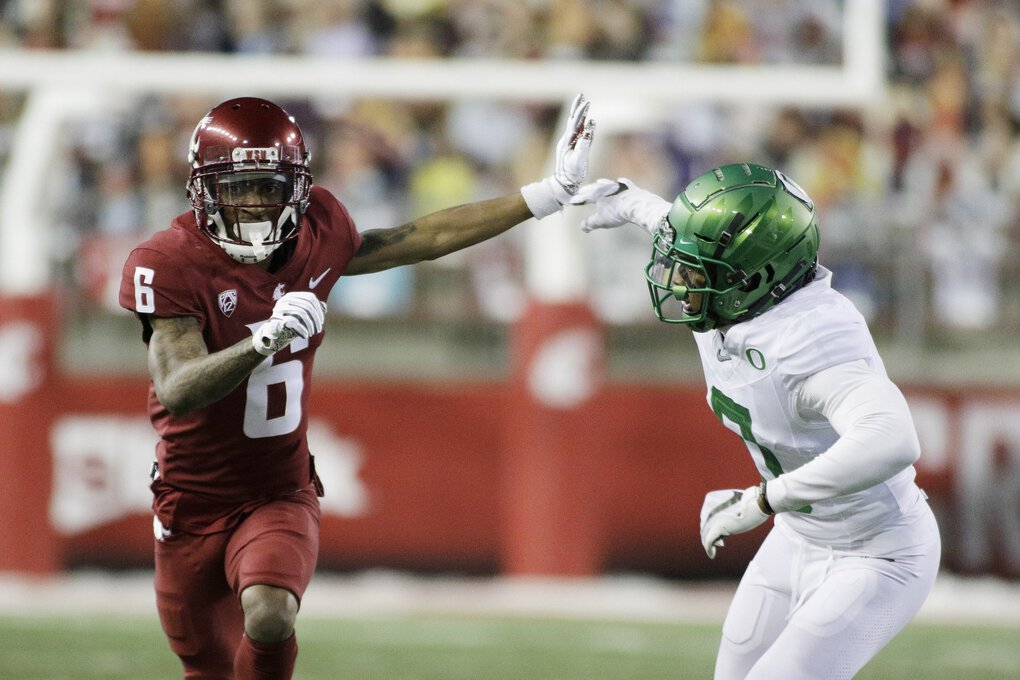 Washington State wide receiver Jamire Calvin, left, runs a route while pressured by Oregon cornerback Deommodore Lenoir during the first half on Nov. 14, 2020. (Young Kwak / The Associated Press)
